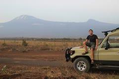 Il viaggiatore caucasico bianco in abiti sportivi si siede in una jeep sui precedenti del Kilimanjaro fotografia stock libera da diritti