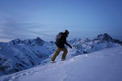 Il viaggiatore con lo zaino e lo snowboard scalano la collina nevosa con la grande vista sulle montagne dell'inverno nella sera Immagine Stock Libera da Diritti