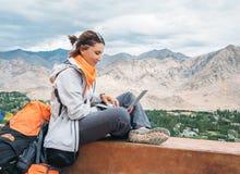 Il viaggiatore con zaino e sacco a pelo con il computer portatile si siede sul punto di vista superiore sotto la montagna Fotografie Stock Libere da Diritti