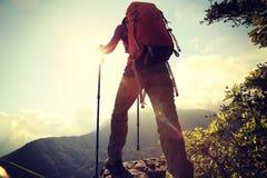 Il viaggiatore con zaino e sacco a pelo della donna gode della vista al picco di montagna Fotografia Stock Libera da Diritti