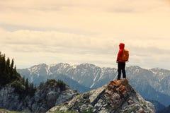 Il viaggiatore con zaino e sacco a pelo della donna gode della vista sul picco di montagna Fotografia Stock