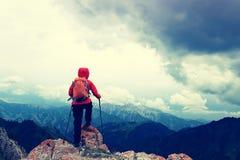 Il viaggiatore con zaino e sacco a pelo della donna gode della vista sul picco di montagna Immagini Stock
