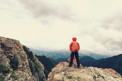 Il viaggiatore con zaino e sacco a pelo della donna gode della vista sul picco di montagna Fotografie Stock