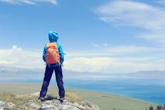 Il viaggiatore con zaino e sacco a pelo della donna gode della vista sul picco di montagna Immagine Stock