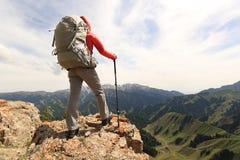 Il viaggiatore con zaino e sacco a pelo della donna gode della vista sulla scogliera del picco di montagna Immagini Stock