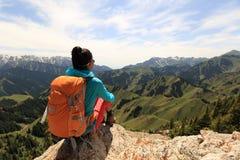 Il viaggiatore con zaino e sacco a pelo della donna gode della vista sulla scogliera del picco di montagna Immagini Stock Libere da Diritti