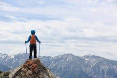 Il viaggiatore con zaino e sacco a pelo della donna gode della vista sulla scogliera del picco di montagna Fotografia Stock Libera da Diritti