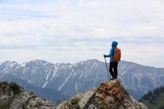 Il viaggiatore con zaino e sacco a pelo della donna gode della vista sulla scogliera del picco di montagna Fotografia Stock