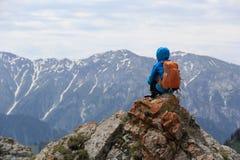 Il viaggiatore con zaino e sacco a pelo della donna gode della vista sulla scogliera del picco di montagna Immagine Stock Libera da Diritti
