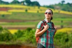 Il viaggiatore con zaino e sacco a pelo della giovane donna cammina sui precedenti dei campi colorati Immagine Stock