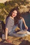 Il viaggiatore con zaino e sacco a pelo della ragazza sta sedendosi sul libro di lettura e della roccia fotografie stock