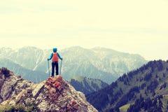 il viaggiatore con zaino e sacco a pelo gode della vista sulla scogliera del picco di montagna Immagine Stock Libera da Diritti