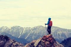 il viaggiatore con zaino e sacco a pelo gode della vista sulla scogliera del picco di montagna Fotografia Stock Libera da Diritti