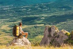Il viaggiatore con zaino e sacco a pelo si siede su roccia e sull'esame della valle Fotografia Stock