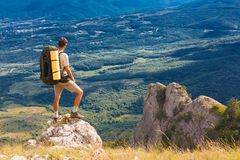 Il viaggiatore con zaino e sacco a pelo sta su roccia e sull'esame della valle Fotografie Stock Libere da Diritti