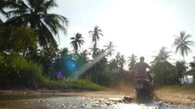 Il viaggiatore del giovane sta conducendo la motocicletta nei giri tropicali della giungla attraverso una pozza Movimento lento E archivi video