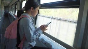 Il viaggiatore dell'adolescente della ragazza con lo zaino fa una pausa la finestra del vagone con lo stile di vita uno smartphon video d archivio