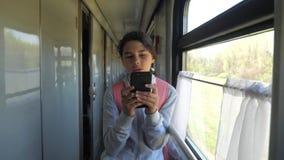 Il viaggiatore dell'adolescente della ragazza con lo zaino fa una pausa la finestra del vagone con uno smartphone Trasporto di vi archivi video