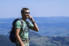 Il viaggiatore dell'uomo parla sul telefono e ride contro lo sfondo delle montagne Immagine Stock