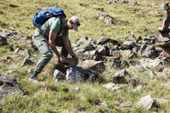 Il viaggiatore dell'uomo pone la sua pietra sul modo alla montagna di Bliznitsa Fotografie Stock Libere da Diritti
