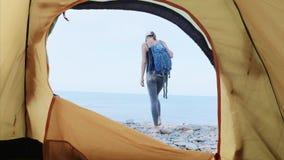 Il viaggiatore della giovane donna prende il suo zaino dalla tenda di campeggio e va dal mare stock footage