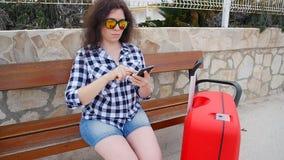 Il viaggiatore della giovane donna si siede ed esamina lo smartphone stock footage