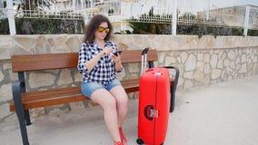 Il viaggiatore della giovane donna si siede ed esamina lo smartphone archivi video