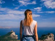 Il viaggiatore della ragazza è indietro sulle vacanze estive contro il mare ed il cielo blu Fotografia Stock Libera da Diritti