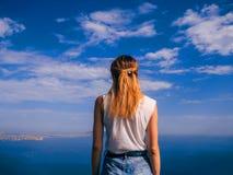 Il viaggiatore della ragazza è indietro sulle vacanze estive contro il mare ed il cielo blu Fotografia Stock