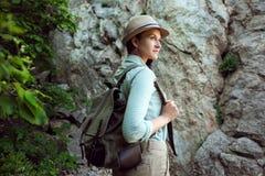Il viaggiatore della ragazza cammina attraverso le montagne ed il legno Sorride Shorts e abbronzatura verdi della camicia Cappell Immagini Stock Libere da Diritti