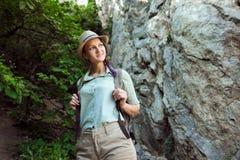 Il viaggiatore della ragazza cammina attraverso le montagne ed il legno Sorride Shorts e abbronzatura verdi della camicia Cappell Fotografie Stock