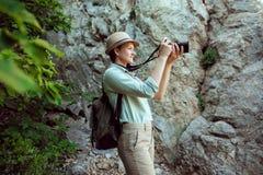 Il viaggiatore della ragazza cammina attraverso le montagne ed il legno Sorride Shorts e abbronzatura verdi della camicia Cappell Fotografia Stock Libera da Diritti