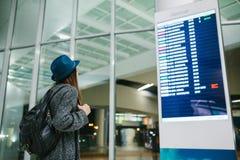 Il viaggiatore della ragazza con uno zaino in un cappello esamina il bordo di informazioni l'aeroporto Ottenere informazioni su Immagine Stock