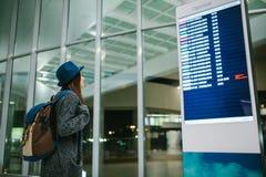 Il viaggiatore della ragazza con uno zaino in un cappello esamina il bordo di informazioni l'aeroporto Ottenere informazioni su Fotografia Stock Libera da Diritti