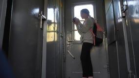 Il viaggiatore della ragazza dell'adolescente con lo zaino fa una pausa la finestra del vagone con uno smartphone Trasporto di vi video d archivio
