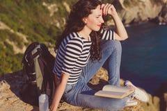 Il viaggiatore della ragazza sta sedendosi sul libro di lettura e della roccia Fotografia Stock