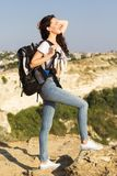 Il viaggiatore della ragazza sta sedendosi sulla roccia con lo zaino immagini stock
