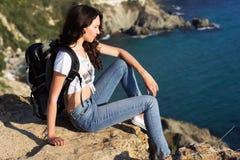 Il viaggiatore della ragazza sta sedendosi sulla roccia sopra la vista del mare fotografia stock libera da diritti
