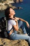 Il viaggiatore della ragazza sta sedendosi sulla roccia sopra la vista del mare fotografie stock