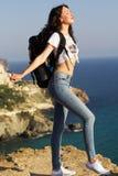 Il viaggiatore della ragazza sta stando sulla roccia con lo zaino Fotografia Stock Libera da Diritti