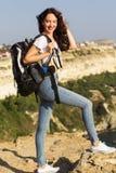 Il viaggiatore della ragazza sta stando sulla roccia con lo zaino Immagine Stock