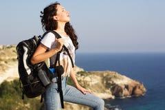 Il viaggiatore della ragazza sta stando sulla roccia con lo zaino Fotografie Stock Libere da Diritti