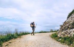 Il viaggiatore di viaggiatore con zaino e sacco a pelo cammina sulla strada Fotografie Stock Libere da Diritti