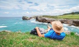 Il viaggiatore di viaggiatore con zaino e sacco a pelo riposa dal mare roccioso e prende mobil p immagine stock