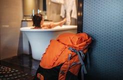 Il viaggiatore di viaggiatore con zaino e sacco a pelo della donna prende un bagno nell'hotel di alta qualità Fotografia Stock