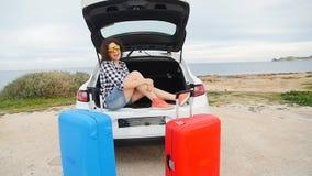 Il viaggiatore felice della donna con le valigie si avvicina alla sua automobile stock footage