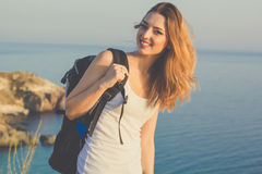 Il viaggiatore felice della ragazza sta stando sulla roccia sopra il mare Fotografia Stock Libera da Diritti