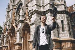 Il viaggiatore felice sta facendo il selfie vicino alla costruzione della cattedrale nella città Fotografia Stock