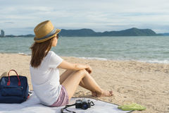 Il viaggiatore femminile che si siede sulla spiaggia che considera il mare ondeggia Fotografia Stock Libera da Diritti