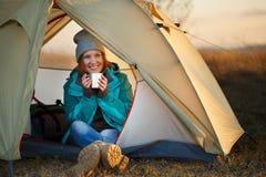Il viaggiatore femminile sorridente negli sport sitti delle scarpe di trekking e dura fotografie stock libere da diritti